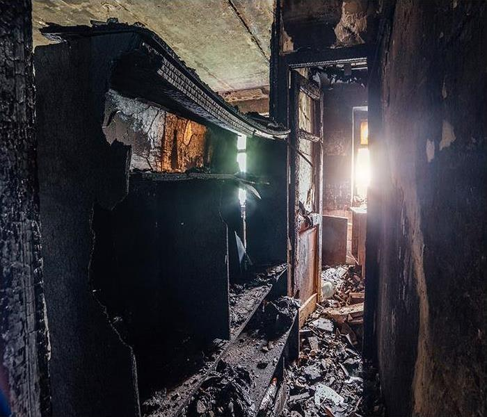 room in house with burned furniture and charred walls in black soot.