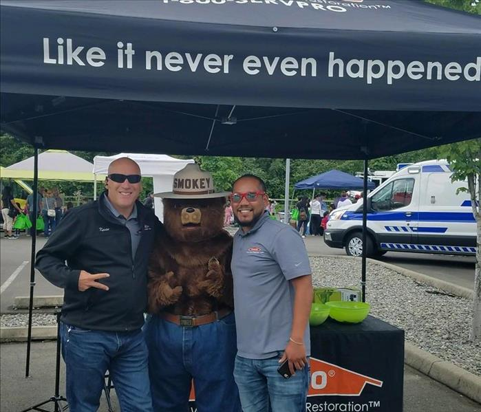 two male employees standing with Smokey the bear under a black SERVPRO tent