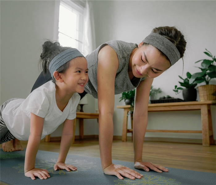 a mother and daughter working out together at home